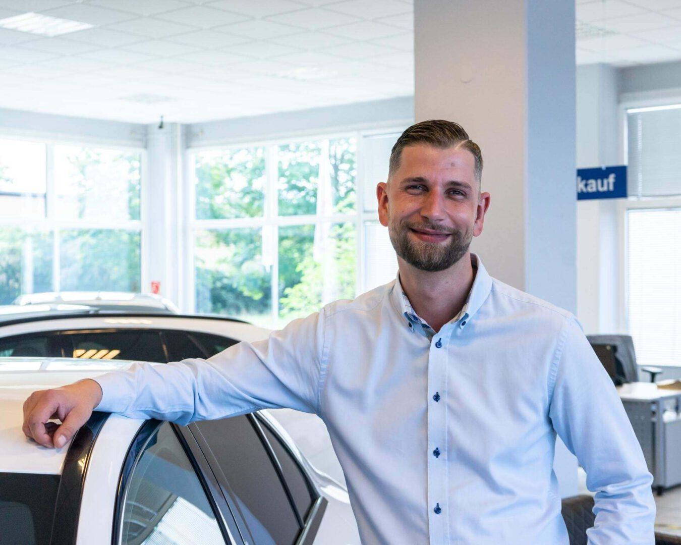 Kundenberater Thomas Müller vor Fahrzeugen