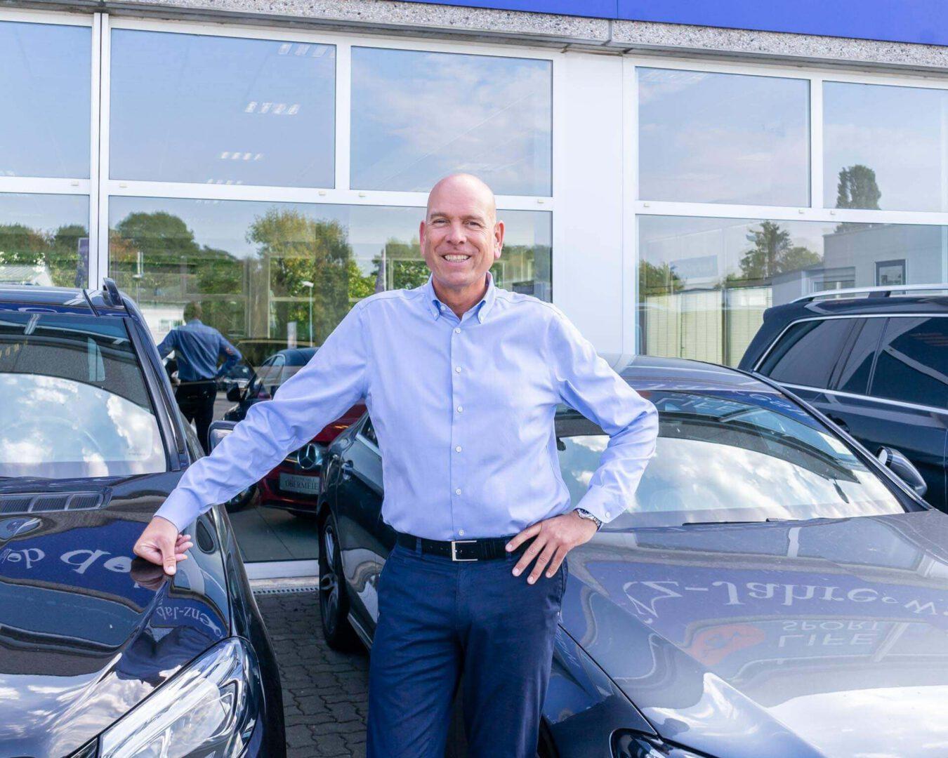 Geschäftsführer Helmut Obermeier vor Fahrzeugen