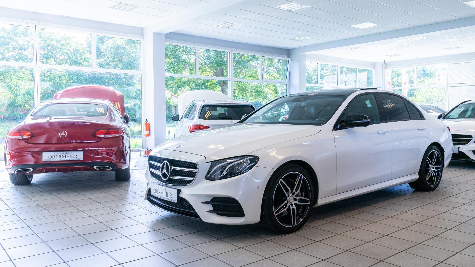 Rotes und weißes Fahrzeug von Mercedes Benz in Ausstellungshalle